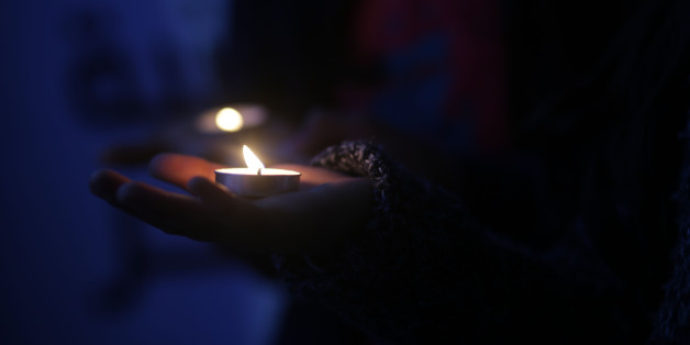 A youth sits next to a cross made of flowers at a candle light vigil in solidarity with Egyptian Christians after attacks targeting two churches, in Gaza City, Monday, April 10, 2017. A double suicide bombing by the Islamic State group against two Christian churches in Egypt killed at least 45 people.    (Photo by Majdi Fathi/NurPhoto via Getty Images)