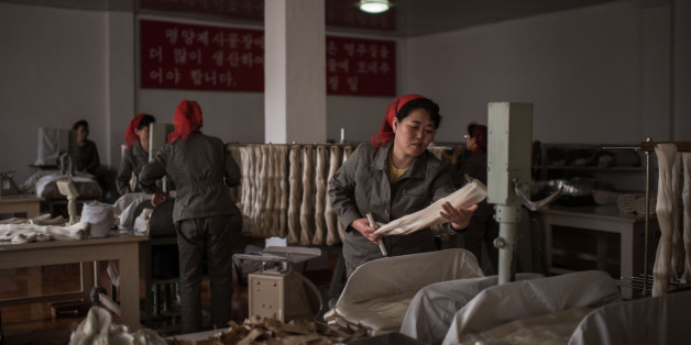 A worker processes silk at the Kim Jong Suk Silk Mill in Pyongyang on February 21, 2017. The Kim Jong Suk Silk Mill employs a workforce of 1,600 people, and is named after the grandmother of current North Korean leader Kim Jong-Un.  / AFP / Ed JONES        (Photo credit should read ED JONES/AFP/Getty Images)