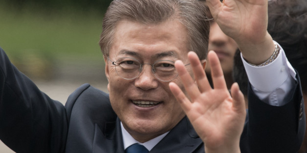 South Korea's President Moon Jae-In waves to his supporters as he greets members of staff as he arrives near the presidential Blue House in Seoul on May 10, 2017.Left-leaning former human rights lawyer Moon Jae-In began his five-year term as president of South Korea following a landslide election win after a corruption scandal felled the country's last leader.  / AFP PHOTO / Ed JONES        (Photo credit should read ED JONES/AFP/Getty Images)