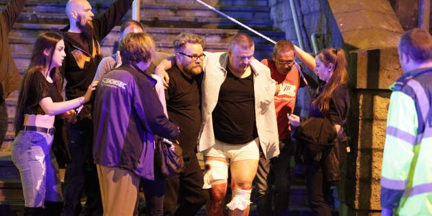 Polizisten helfen einem Verletzten nach der Explosion auf dem Ariana-Grande-Konzert in Manchester