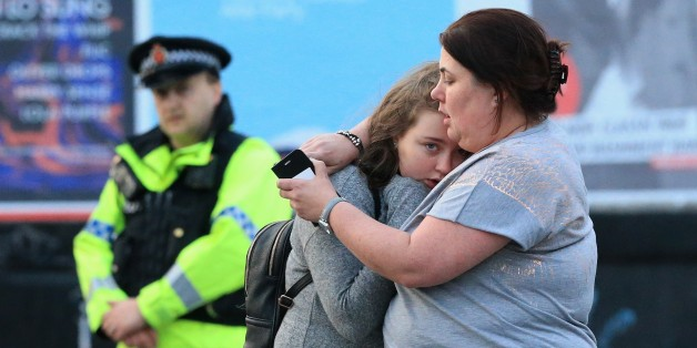 MANCHESTER, UNITED KINGDOM - MAY 23: Walking casualties Vikki Baker and her thirteen year old daughter Charlotte hug outside the Manchester Arena stadium in Manchester, United Kingdom on May 23, 2017. A large explosion was reported at the end of a concert by American singer Ariana Grande. So far, police have confirmed 20 dead and over fifty injured in the explosion, now thought to be terrorist-related.  (Photo by Lindsey Parnaby/Anadolu Agency/Getty Images)