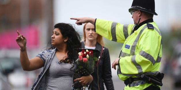 A police officer (R) directs a woman carrying a bunch of flowers near the Manchester Arena in Manchester, northwest England on May 23, 2017 following a deadly terror attack at the concert at the venue the night before. Twenty two people have been killed and dozens injured in Britain's deadliest terror attack in over a decade after a suspected suicide bomber targeted fans leaving a concert of US singer Ariana Grande in Manchester. / AFP PHOTO / Oli SCARFF        (Photo credit should read OLI SCAR