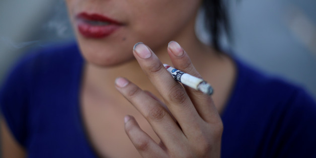 A woman smokes a Pall Mall cigarette in Ciudad Juarez, Mexico May 11, 2017. Picture taken May 11, 2017. REUTERS/Jose Luis Gonzalez