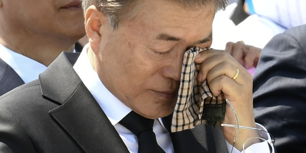 South Korean President Moon Jae-in wipes a tear from his eyes during the annual Democratic uprising memorial at the Gwangju National Cemetery, in the southwestern city of Gwangju on May 2017, as the government holds an annual ceremony to mark the 37th anniversary of a pro-democracy uprising. Moon commemorated the anniversary of the 1980 pro-democracy uprising in the city of Gwangju where hundreds of protestors were killed by the military. / AFP PHOTO / POOL / Kim Min-Hee        (Photo credit sho