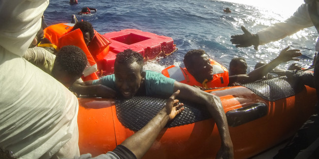LAMPEDUSA, ITALY - MAY 24:  Refugees and migrants are pulled onboard a rescue craft by crewmembers from the Migrant Offshore Aid Station (MOAS) 'Phoenix' vessel after a wooden boat bound for Italy carrying more than 500 people capsized on May 24, 2017 off Lampedusa, Italy. The Migrant Offshore Aid Station (MOAS) 'Phoenix' vessel rescued 603 people after one of three wooden boats partially capsized leaving more than 30 people dead. Numbers of refugees and migrants attempting the dangerous central