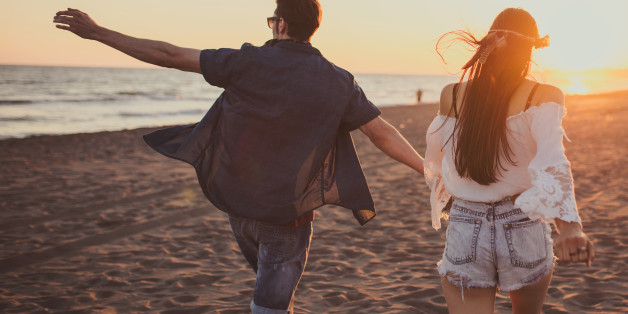 Couple running free on the beach while holding hands