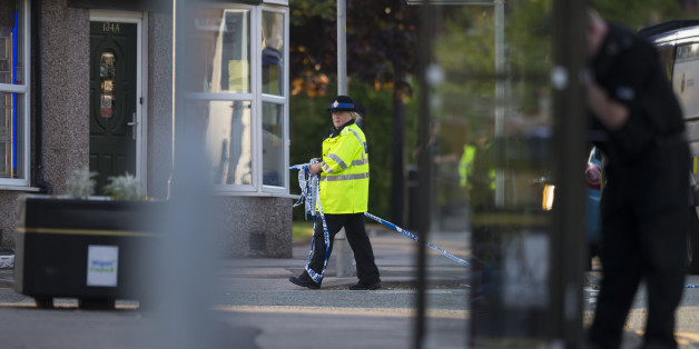 A policewoman gathers police tape during a security operation at Springfield Street in Wigan, Greater Manchester on May 25, 2017.  / AFP PHOTO / Jon Super / JON SUPER        (Photo credit should read JON SUPER/AFP/Getty Images)