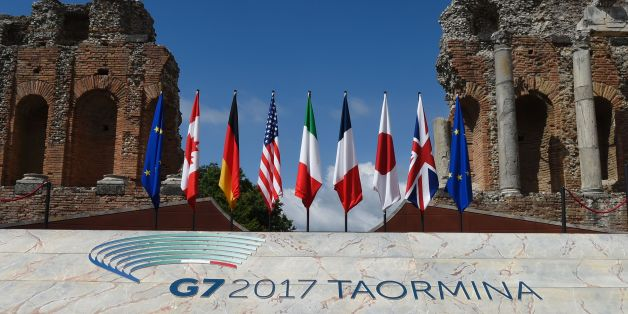 A picture shows flags on the stage of the ancient Greek Theater where Heads of State and of Government of the G7, the group of most industrialized economies, will pose for a family picture, on May 26, 2017 in Taormina, Sicily.The leaders of Britain, Canada, France, Germany, Japan, the US and Italy will be joined by representatives of the European Union and the International Monetary Fund (IMF) as well as teams from Ethiopia, Kenya, Niger, Nigeria and Tunisia during the summit from May 26 to 27,