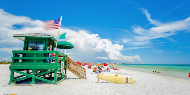 A lifeguard tower at an idyllic beach in a sunny summer day. Siesta Key beach at Sarasota, Florida, USA in the Gulf of Mexico. Emerald water and white sand with a national american flag in the wind.
