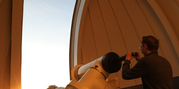 A man takes a picture through a telescope of Venus transiting across the Sun at the Vienna Urania observatory in Vienna on June 6, 2012. Sky-gazers around the world held up their telescopes and viewing glasses on June 6 to watch Venus slide across the sun -- a rare celestial phenomenon that will not happen again for more than 100 years. The spectacle began shortly after 2200 GMT on June 5 in parts of North America, Central America and the northern part of South America, and was seen, with magnif