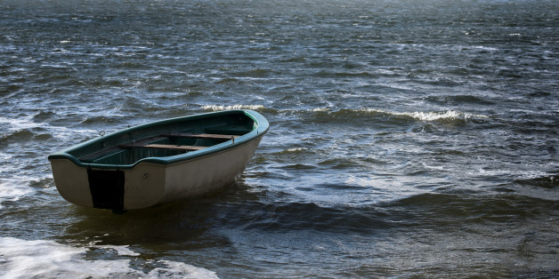 Empty rowboat floats lonely on the sea waves to the clouds at the wide horizon, seascape with copy space in the water