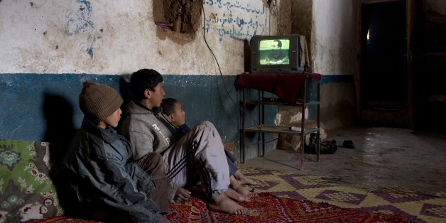 Children watch TV in their house in Tilmi village in the High Atlas region of Morocco February 13, 2015. The snowy foothills of the High Atlas mountains in Morocco are home to several Berber villages where the inhabitants make their living by farming, baking bread in traditional ovens, herding cattle, and the making and selling of honey, olive oil and pottery. Extreme weather fluctuations and erosion that causes flooding and landslides have led to a drop in agricultural productivity, the United