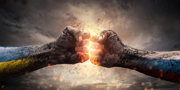 Close up of two fists hitting each other over dramatic sky