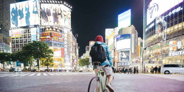 Young guy with backpack riding a bike on Shibuya crossing in Tokyo, Japan
