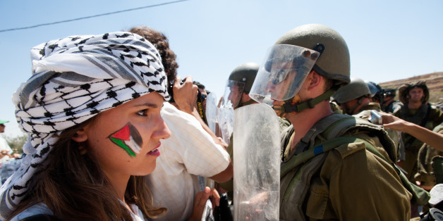 Al-Masara, Occupied Palestinian Territories - August 24, 2012: Italian solidarity activists join Palestinians confronting heavily armed Israeli soldiers in a weekly nonviolent demonstration against the separation barrier that would cut off the West Bank village of Al Ma'sara from its agricultural lands.