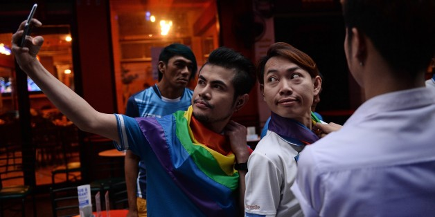 Members of the LGBT community in Thailand take photos as they gather in Bangkok on June 18, 2016 to take part in a vigil for victims of the worst mass shooting in modern US history in Orlando, Florida.Forty-nine people were killed and 53 wounded when a 29-year-old man ran amok in a packed gay nightclub early on June 12 in Orlando, armed with a legally bought assault rifle. / AFP / LILLIAN SUWANRUMPHA        (Photo credit should read LILLIAN SUWANRUMPHA/AFP/Getty Images)