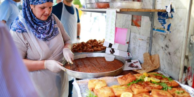 A woman prepares food for Ramadan on May 27, 2017 at a market, in the Barbes area of northern Paris. 