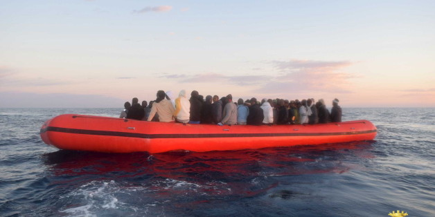 Migrants sit in their boat during a rescue operation of 219 migrants by Italian naval vessel Bettica (not seen) in this February 23, 2016 handout picture provided by Marina Militare. More than 700 migrants were rescued from six leaky boats in the sea between Tunisia and Sicily on Tuesday and four were found dead, the Italian navy said. REUTERS/Marina Militare/Handout via Reuters ATTENTION EDITORS - THIS PICTURE WAS PROVIDED BY A THIRD PARTY. REUTERS IS UNABLE TO INDEPENDENTLY VERIFY THE AUTHENTI