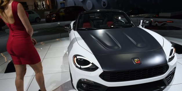 A model stands next to the Fiat 124 Spider during the New York International Auto Show at the Javits center in New York on April 13, 2017.  / AFP PHOTO / TIMOTHY A. CLARY        (Photo credit should read TIMOTHY A. CLARY/AFP/Getty Images)