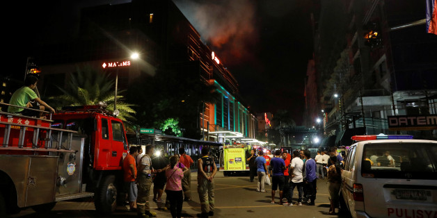 Evacuated employees and guests of hotels stand along a road and watch as smoke billows from a Resorts World building in Pasay City, Metro Manila, Philippines June 2, 2017. REUTERS/Erik De Castro     TPX IMAGES OF THE DAY