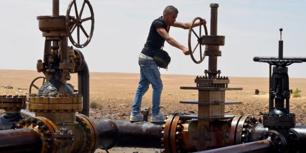 A local turns the wheel of a petroleum pumping station in El Kamour, in Tunisia's southern state of Tatatouine, on May 24, 2017, as protestors continue to stage a sit-in outside the oil and gas plant to demand for a share of the resources and employment in the sector. Since April 23, 2017, hundreds of protesters have blocked traffic on the road leading to the oilfields in Tataouine and erected tents at a sit-in outside el-Kamour, demanding the allocation of 70 percent of jobs in the petroleum se