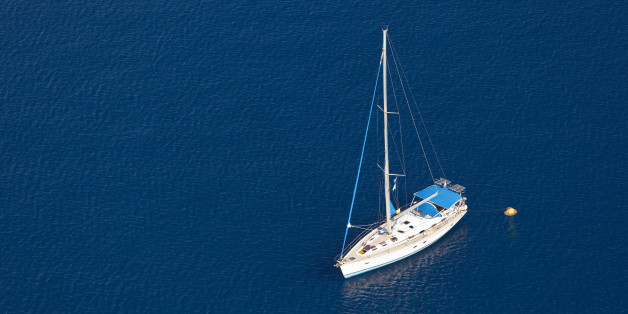 Looking down to the sea with a single sailboat, Santorini.