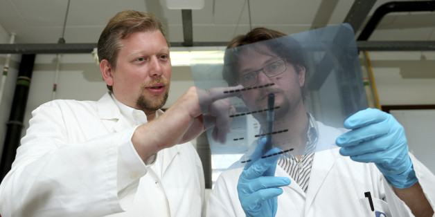 Belgian researcher Pierre Sonveaux stands next to his team member Paolo Porporato (R) of Italy as they examine a readout on a photographic film at the University of Louvain's Institute of Experimental and Clinical Research in Brussels July 31, 2014. According to the institute, the researchers have reached a breakthrough in preventing cancer tumours from spreading.  REUTERS/Francois Lenoir (BELGIUM - Tags: HEALTH SOCIETY SCIENCE TECHNOLOGY)