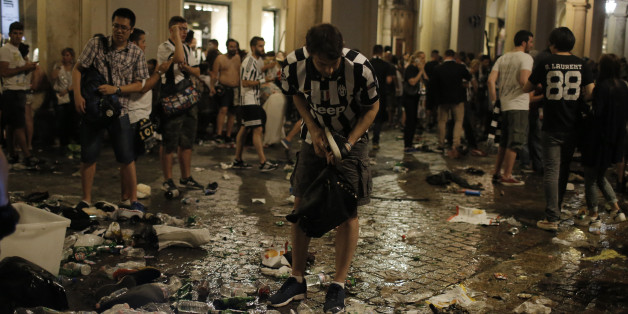Juventus' supporters look for personal belongings in Piazza San Carlo after a panic movement in the fanzone where thousands of Juventus fans were watching the UEFA Champions League Final football match between Juventus and Real Madrid on a giant screen, on June 3, 2017in Turin. / AFP PHOTO / Marco BERTORELLO        (Photo credit should read MARCO BERTORELLO/AFP/Getty Images)