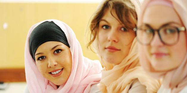 Groupe multiethnique d'adolescentes dans leur salle de classe de l'école secondaire.