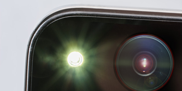 close up of  the camera part of  a smartphone during a picture with flash, the big flash creates a lensflare