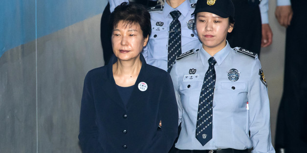 Park Geun-hye, former president of South Korea, left, is escorted by prison officers as she arrives at the Seoul Central District Court in Seoul, South Korea, on Tuesday, May 23, 2017. South Korean prosecutors arrested Park over allegations that she abused her powers and colluded with her longtime friend and former aides to get bribes from the nation's top businesses. Photographer: SeongJoon Cho/Bloomberg via Getty Images