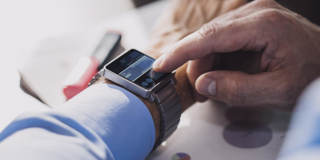 Businessman using smart watch to check stock exchange prices.