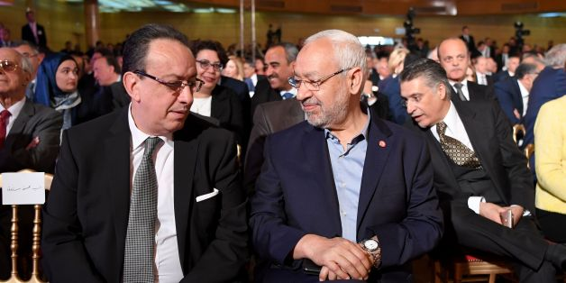 Hafedh Caid Essebsi (L), leader of Nidaa Tounes party, talks with Tunisian Islamist Ennahdha party leader Rached Ghannouchi, as they attend an official speech delivered by the Tunisian President Beji Caid Essebsi (unseen) on May 10, 2017 in Tunis.