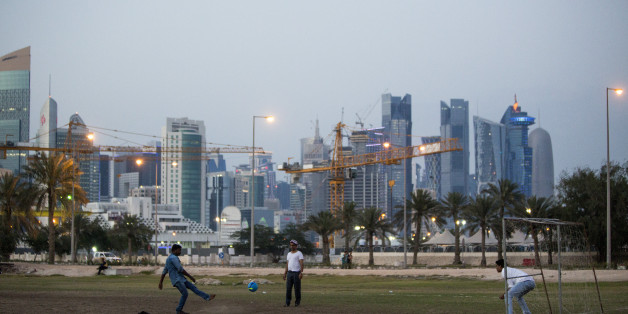 DOHA, QATAR - APRIL 09: Migrant workers play football on an area of wasteland beneath the sky scrapers of Doha's West Bank on April 09, 2016 in Doha, Qatar. (Photo by Charlie Crowhurst/Getty Images)