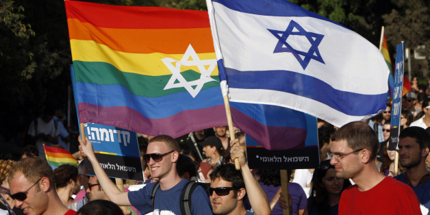 Participants hold flags during the gay pride parade in Jerusalem July 29, 2010. This year's parade marks the one-year anniversary of a shooting attack in a gay and lesbian youth center in Tel Aviv, in which two people were killed and 13 were injured. REUTERS/Ronen Zvulun (JERUSALEM - Tags: POLITICS SOCIETY)