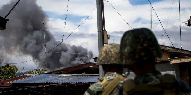 Philippine marines look at smoke following an airstrikes by Philippine Air Force in Marawi, southern Philippines on June 9, 2017. Philippine military jets fired rockets at militant positions on Friday as soldiers fought to wrest control of the southern city from gunmen linked to the Islamic State group.(Photo by Richard Atrero de Guzman/NurPhoto via Getty Images)