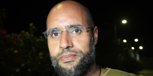 Saif al-Islam Kadhafi, son of Libyan leader Moamer Kadhafi, appears in front of supporters and journalists at his father's residential complex in the Libyan capital Tripoli in the early hours of August 23, 2011. Seif al-Islam, wanted by the International Criminal Court for crimes against humanity and who ICC prosecutor Luis Moreno-Ocampo earlier said had been arrested by the rebels, claimed the insurgents had suffered 'heavy casualties' when they stormed Kadhafi's Bab al-Azizya compound in Tripo