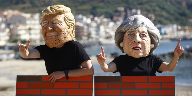 Protesters wear masks depicting U.S. President Donald Trump and Britain's Prime Minister Theresa May during a demonstration against a G7 summit organised by Oxfam in Giardini Naxos near Taormina, Sicily, Italy, May 27, 2017. REUTERS/Yara Nardi