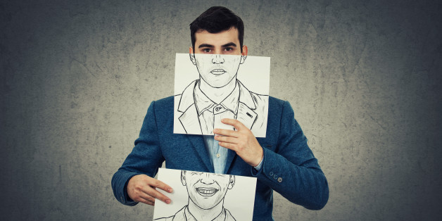 Businessman holding two white papers with different emotions drawn, one hiding half face with angry expressionon and another with a happy, smiling face. Switch mask to hide identity concept.
