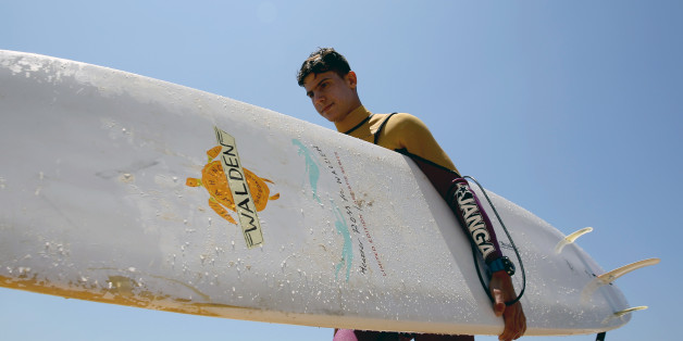 Ali Kassem, a 17-year-old Syrian refugee, carries his surfboard on a beach in the town of Jiyeh, south of the Lebanese capital Beirut, on May 24, 2017.Ali Kassem had never seen the sea before he fled his home in Syria for Lebanon, but now he's a regular in the waves and dreams of his own surf school. / AFP PHOTO / JOSEPH EID        (Photo credit should read JOSEPH EID/AFP/Getty Images)