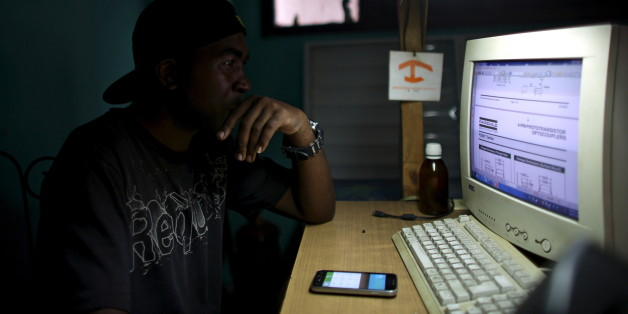 Informatics technician Yurkel Medina, 36, studies about new technologies at the mobile phone repair shop where he works in downtown Havana, February 23, 2016. REUTERS/Alexandre Meneghini
