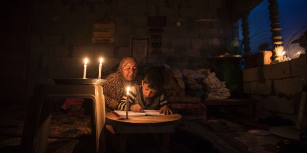 A Palestinian woman helps her son study, by candlelight, at their makeshift home in the Khan Yunis refugee camp in the southern Gaza Strip on April 19, 2017. The Gaza Strip's only functioning power plant was out of action earlier in the week after running out of fuel, the head of the territory's electricity provider told AFP. / AFP PHOTO / MAHMUD HAMS        (Photo credit should read MAHMUD HAMS/AFP/Getty Images)
