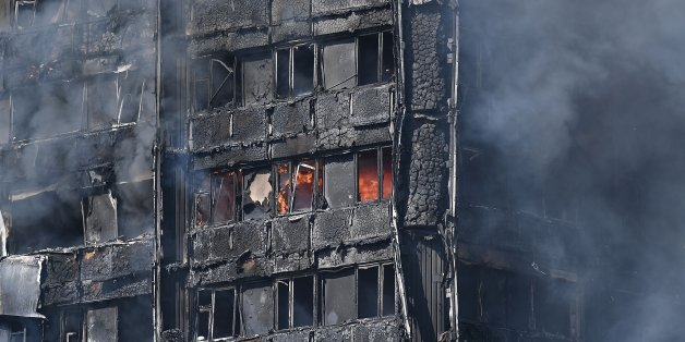 LONDON, ENGLAND - JUNE 14:  Smoke continues to rise from the burning 24 storey residential Grenfell Tower block in Latimer Road, West London on June 14, 2017 in London, England.  The Mayor of London, Sadiq Khan, has declared the fire a major incident as more than 200 firefighters are still tackling the blaze while at least 50 people are receiving hospital treatment.  (Photo by Carl Court/Getty Images)
