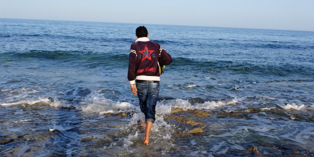 "A Tunisian man, who considered illegal migration to Europe, walks at the water's edge at coastal town Zarzis in southeastern Tunisia February 18, 2011. Tunisia has deployed soldiers to stop a tide of illegal immigrants trying to reach Italy, a military source said Monday, after Rome said a revolution in the north African country had set off a ""biblical exodus."" REUTERS/Anis Mili (TUNISIA - Tags: POLITICS SOCIETY)"