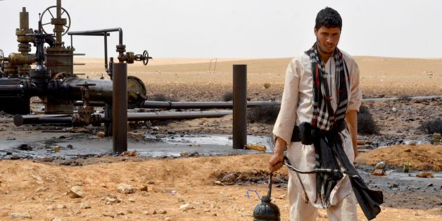 A local walks near a petroleum pumping station in El Kamour, in Tunisia's southern state of Tatatouine, on May 24, 2017, as protestors continue to stage a sit-in outside the oil and gas plant to demand for a share of the resources and employment in the sector. Since April 23, 2017, hundreds of protesters have blocked traffic on the road leading to the oilfields in Tataouine and erected tents at a sit-in outside el-Kamour, demanding the allocation of 70 percent of jobs in the petroleum sector for