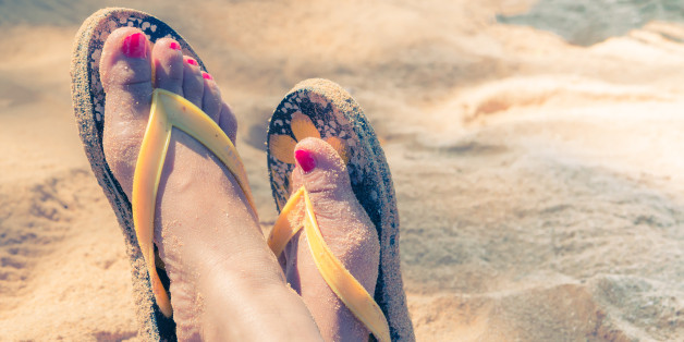 Young girl legs and flip-flop on the sand beach in summer