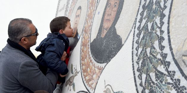 TOPSHOT - Mohamed, the son of Tunisian policeman Aymen Morjane who got killed last year in a jihadist assault on the Bardo museum, kisses a memorial bearing the portrait of his father outside the museum in Tunis on March 18, 2016, as the country marks the first anniversary of the attack. / AFP / FETHI BELAID        (Photo credit should read FETHI BELAID/AFP/Getty Images)