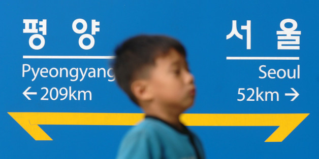 SOUTH KOREA - OCTOBER 08:  A South Korean child walks past a sign which indicates the distance between Korea?s two capitals of Seoul and Pyeongyang, at Imjingang Station near the Demilitarized Zone (DMZ) in Paju, South Korea on Sunday, October 8, 2006. Japanese Prime Minister Shinzo Abe said North Korea must halt plans to test a nuclear weapon as he began a visit to China and South Korea to mend frayed relations.  (Photo by Seokyong Lee/Bloomberg via Getty Images)