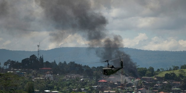 A helicopter flies through smoke billowing from houses after aerial bombings by Philippine Airforce planes on Islamist militant positions in Marawi on the southern island of Mindanao on June 17, 2017.Philippine troops pounded Islamist militants holding parts of southern Marawi city with air strikes and artillery on June 17 as more soldiers were deployed and the death toll rose to more than 300 after nearly a month of fighting. / AFP PHOTO / Noel CELIS        (Photo credit should read NOEL CELIS/