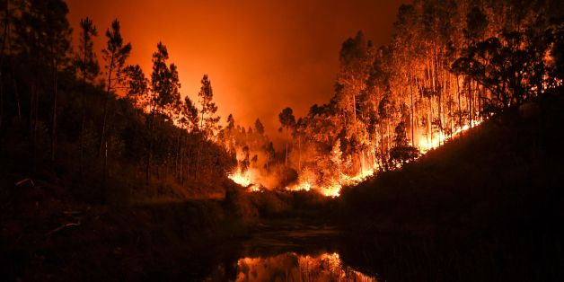 TOPSHOT - A wildfire is reflected in a stream at Penela, Coimbra, central Portugal, on June 18, 2017.  A wildfire in central Portugal killed at least 25 people and injured 16 others, most of them burning to death in their cars, the government said on June 18, 2017. Several hundred firefighters and 160 vehicles were dispatched late on June 17 to tackle the blaze, which broke out in the afternoon in the municipality of Pedrogao Grande before spreading fast across several fronts.  / AFP PHOTO / PATRICIA DE MELO MOREIRA        (Photo credit should read PATRICIA DE MELO MOREIRA/AFP/Getty Images)